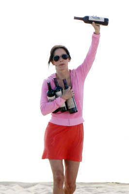 """**EXCLUSIVE**Courtney Cox holds four bottles of wine on the set of """"Cougar Town"""" with the rest of the cast at a beach in Los Angeles"""
