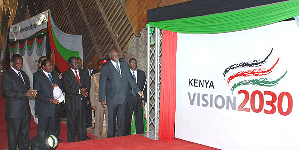 Former President Mwai Kibaki flanked by Former Prime Minister Rt. Hon. Raila Odinga, Former Vice President Hon. Kalonzo Musyoka and Former Minister for Planning Hon. Wycliffe Oparanya unveiling the Vision 2030 Logo after he officially launched the vision and its First Medium Term plan at KICC, Nairobi. Courtesy of Business Daily