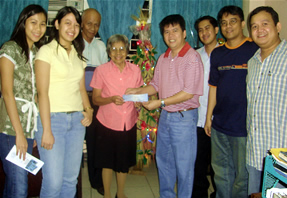Brandstream Manager Raymond Abcede gives check to MCCID Registrar Remedios Esposa
