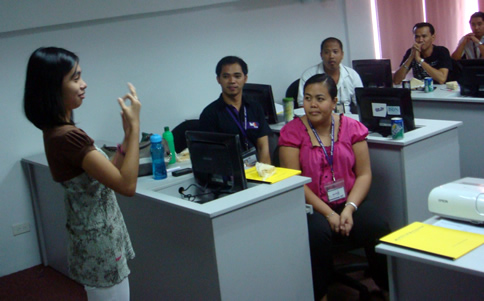 Maricris Siping instructs trainees on fingerspelling.