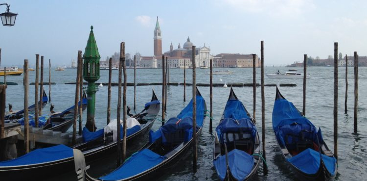 view of gondolas and the city of Venice Italy