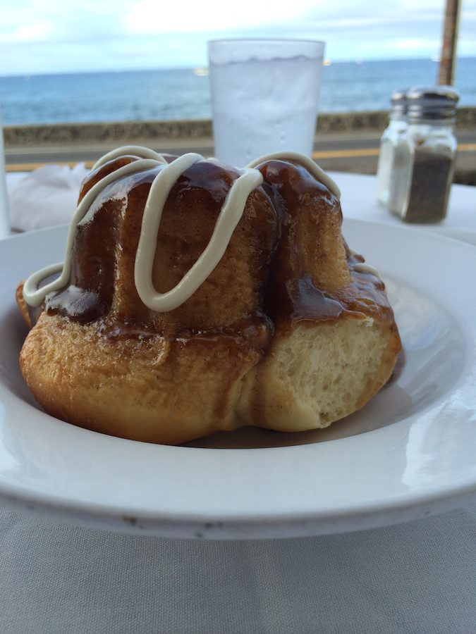 closeup of cinnamon roll with ocean in background