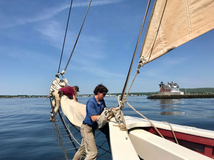 Crew works on the Windjammer sails as we pass a lighthouse in Rockland Maine