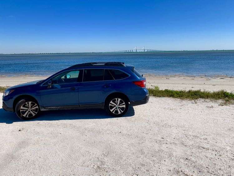Subaru Outback Fort DeSoto beach sand with view of Sunshine Skyway Bridge