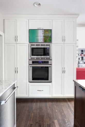 White kitchen with Thermador convection oven and microwave stack with Samsung HDTV above