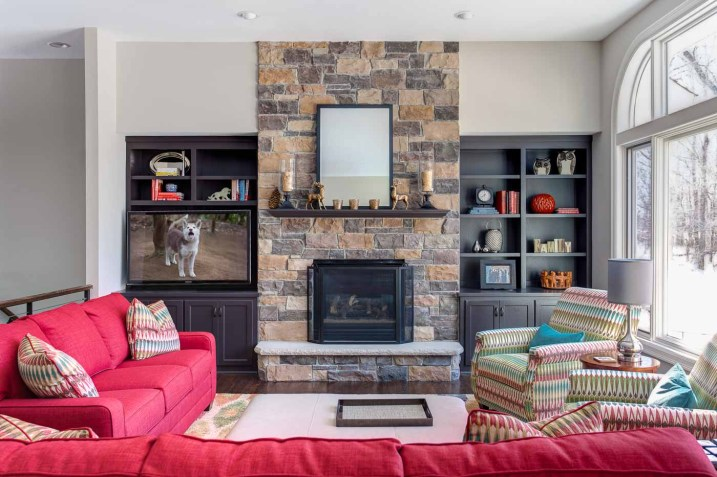 Large living room with a fireplace with stone surround and built-in bookcases