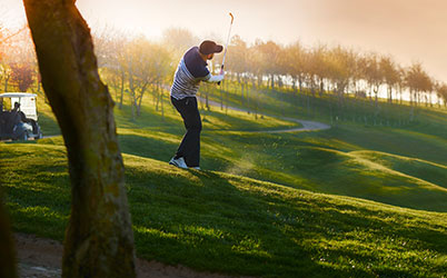 Male golfer on a golf course mid swing