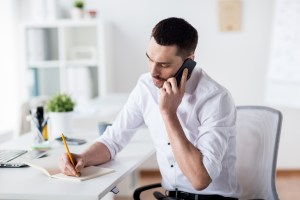 man on phone while writing in notebook