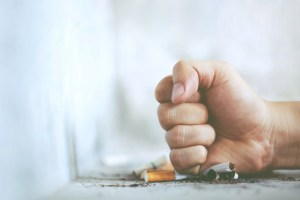 person crushing cigarette with fist