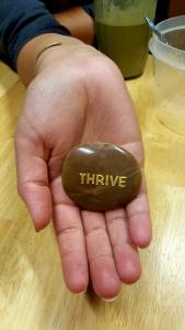 Prayer stone with engraved word thrive.
