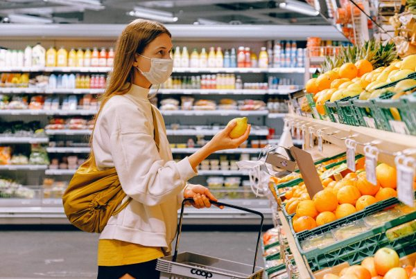 woman in yellow tshirt and beige jacket holding a fruit 3962285 scaled