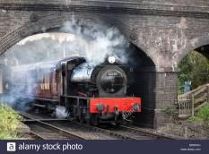 steam-train-passing-under-brick-bridge
