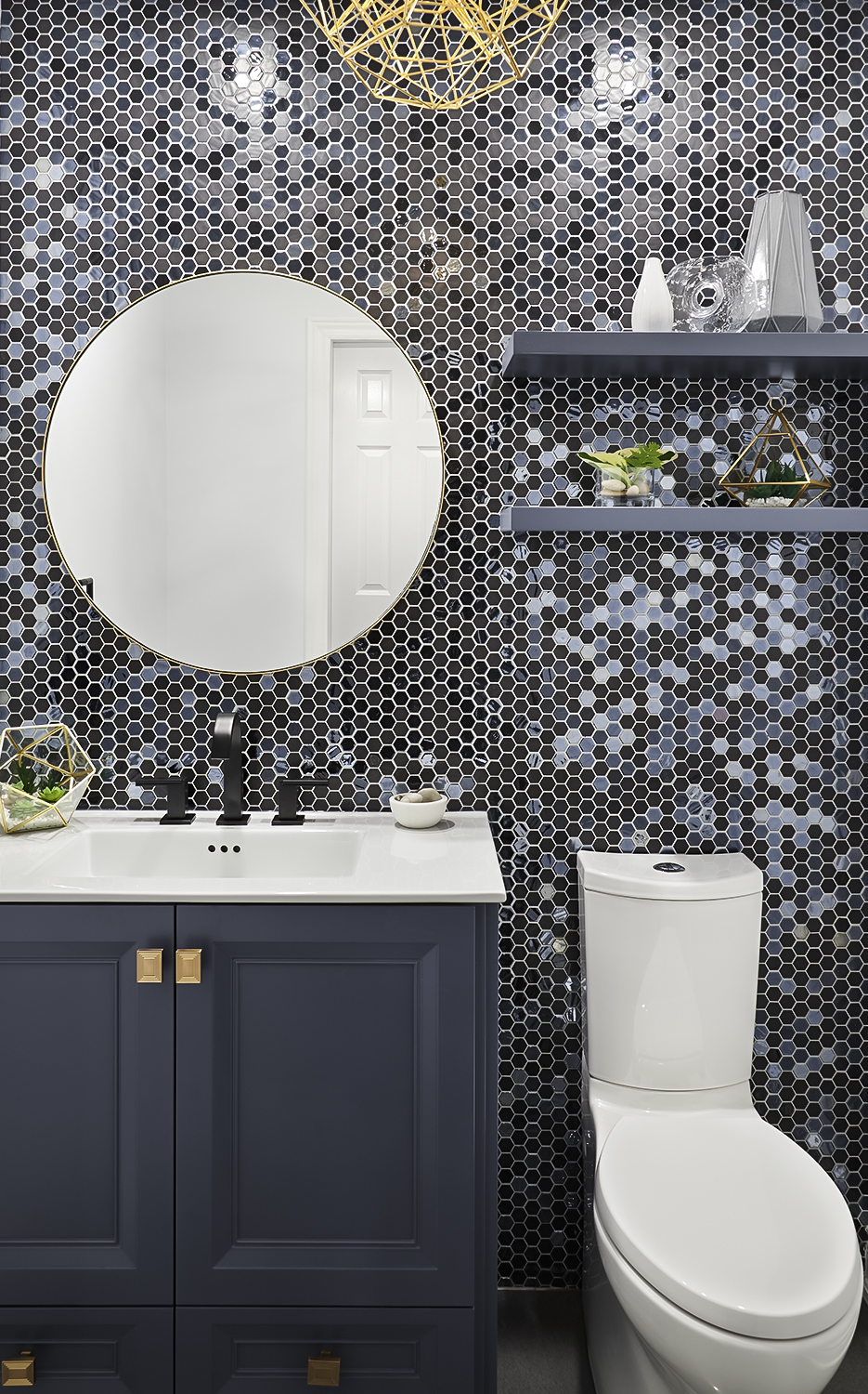 Indigo Vanity, champagne gold hardware, circular mirror, Kohler toilet, floating shelves and stunning feature Tile