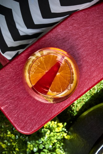 Red Composite Muskoka Chair and brandy citrus summer cocktail