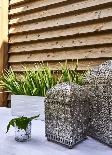 Exterior ornate Morrocan Tin Lanterns, everlasting table planter styled infront of this gorgeous wood slat privacy barrier
