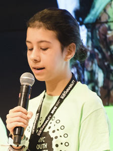 A picture of Anna Kathawala speaking with a microphone. She is wearing a green t-shirt and a black lanyard.