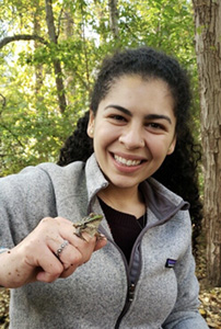 Giselle Herrera is standing in front of a tree. She is wearing a grey fleece jacket. She is smiling and holding a frog in her right hand.