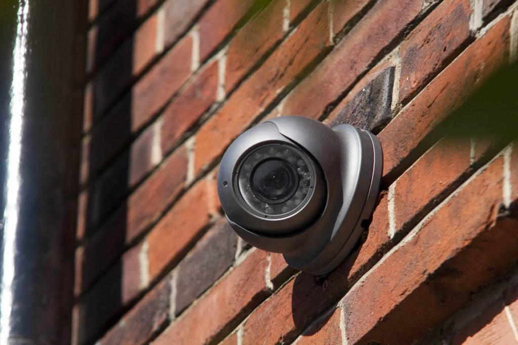 CCTV camera fixed to brick wall of house in London