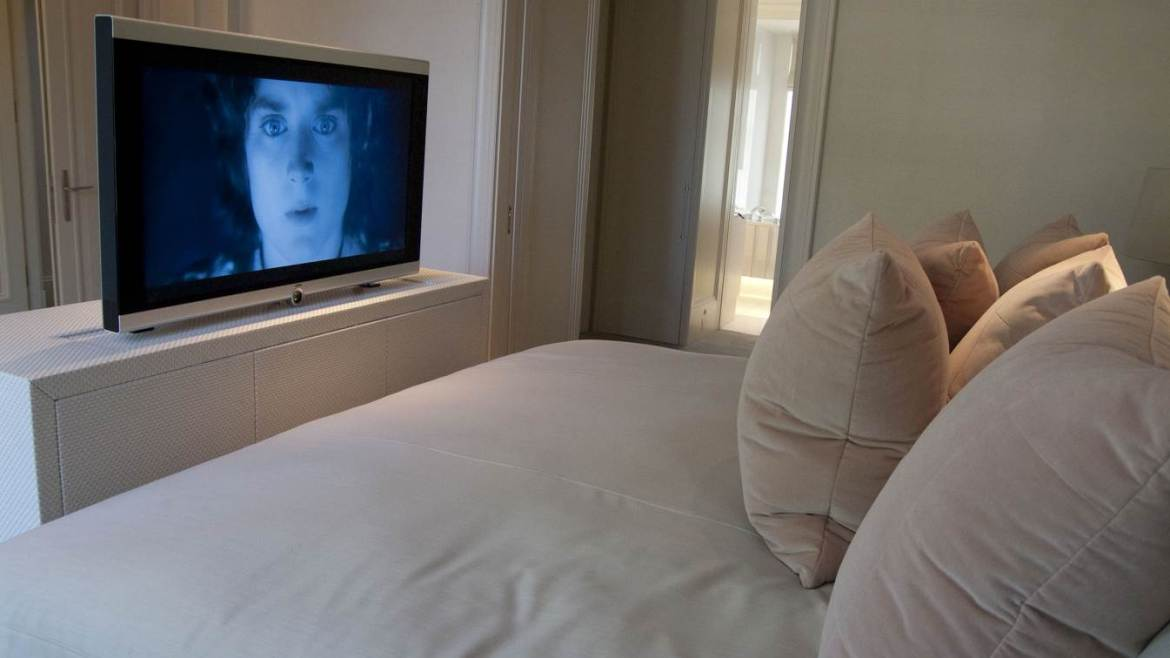 Closeup of bed with TV and unit