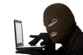Visual presentation of hacker dressed in balaclava accessing computer