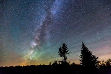 The Galactic Center of the Milky Way, surrounded by colorful airglow, seen from the top of Cadillac Mountain in Acadia National Park, Mount Desert Island, Maine.