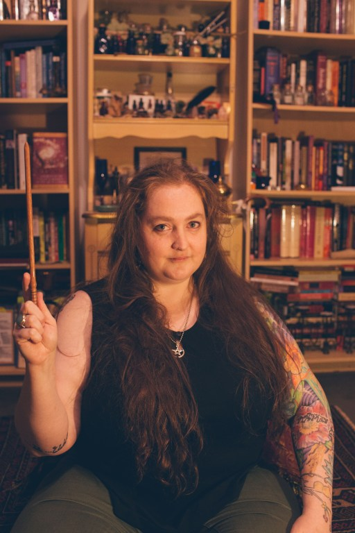 A picture of Witch and Pagan Meagan Angus in front of her altar and bookshelves, holding up a wand, looking knowingly into the camera. She is wearing a pentagram necklace, a black tank top and green pants, with long flowing red hair.