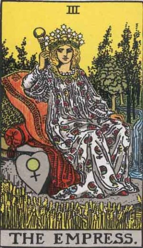 The Empress, Pamela Colman Smith Waite Tarot. A blond light skinned femme sits on a comfy seat with lots of pillows. She is surrounded by golden grains, evergreen trees A blue stream runs behind her. She wears a crown of stars, a white robe with a pattern of red pomegranates, and holds a small golden scepter. At her feet is a shield with the symbol for Venus.