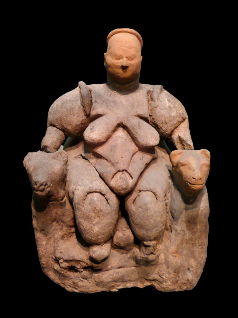 Megalesia. The Seated Woman of Çatalhöyük, aprox 6,000 BCE. A tiny red clay sculpture of a nude person with big breasts, a big round belly, thick arms and thick legs. They are seated on a throne with lions' heads on the armrests.