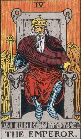 The Emperor Card, Pamela Colman Smith-Waite Tarot. An older masculine person with a white beard sits on a gray stone throne. There are rams heads on the back and armrests. They are on a mountaintop. Yellow mountains in the background with an orange sky. The person is wearing silver armor, with a maroon cloak and red skirt. They wear a gold crown. They hold a gold scepter and orb. They are looking straight at you.