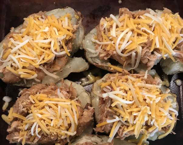 Sprinkle cheese over the Twice Baked Shredded BBQ Chicken potatoes.