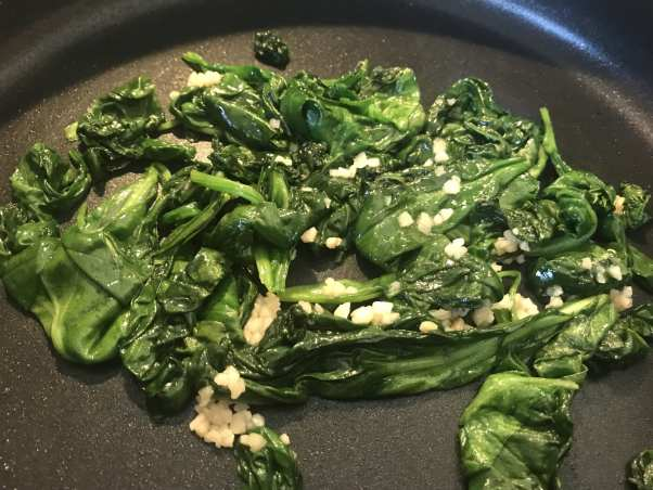 Cook the spinach and garlic.