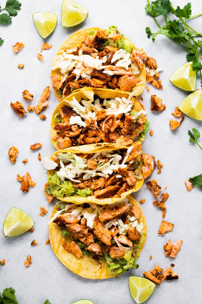 tacos in a line stuffed with salmon.