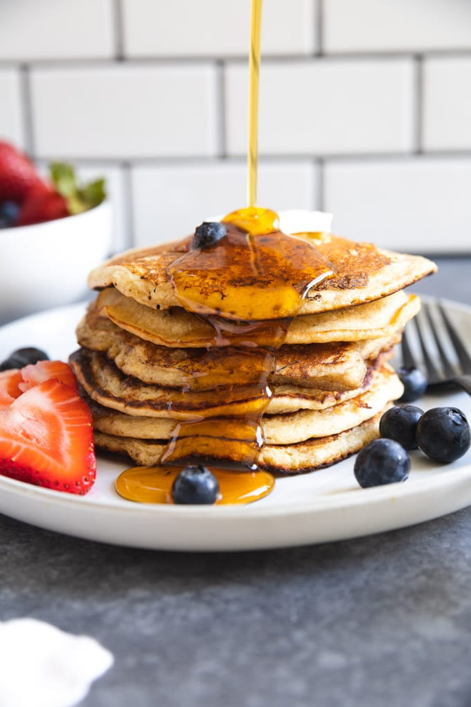 syrup being poured onto a stack of pancakes