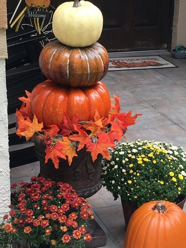 pumpkin topiary along side a splat witch on the front porch.