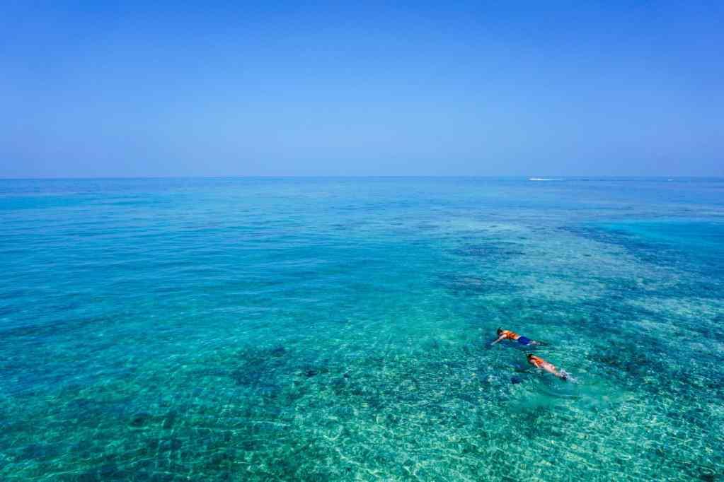 two people snorkeling in blue ocean water