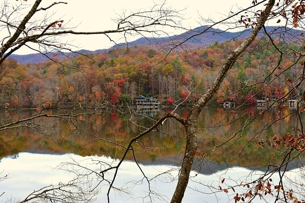 Forest in fall with lakehouse reflected in the lake and branches in the foreground