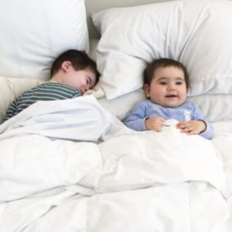 having second child: brother and baby sister next to each other in parent's bed