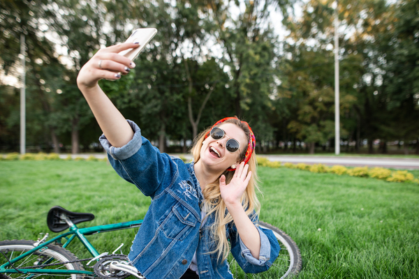 Woman taking a selfie outside next to a bicycle.