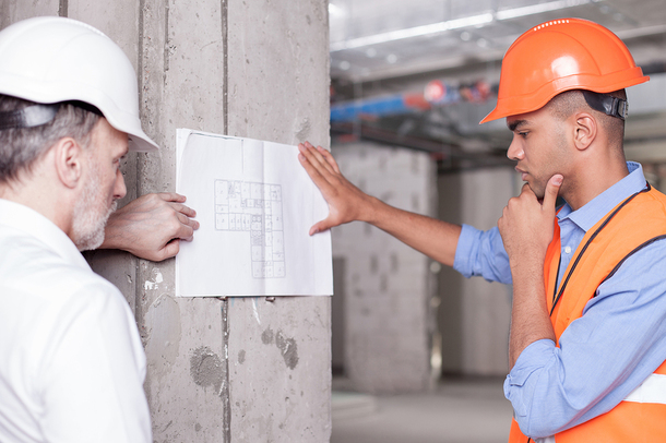 Two construction workers looking at building plans.