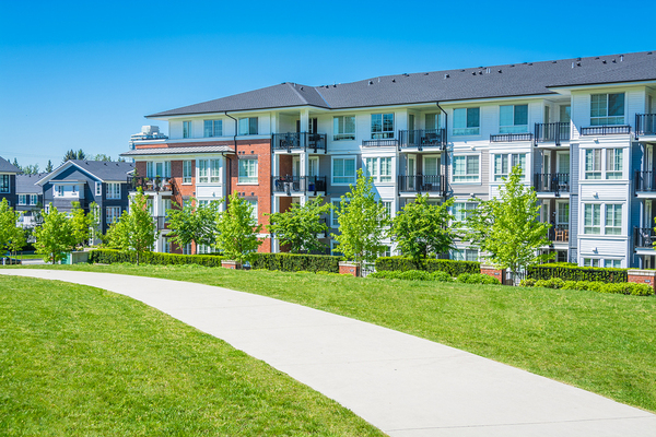 View of condominiums with a pathway in front and green grass.