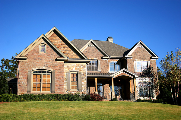 Beautiful brick front home with green lawn in the front.