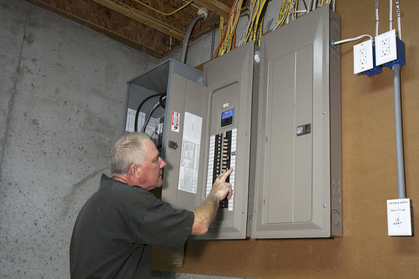 Man looking at an electrical box.