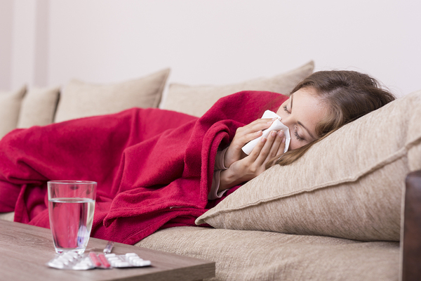 Woman lying on the couch blowing her nose with a tissue.