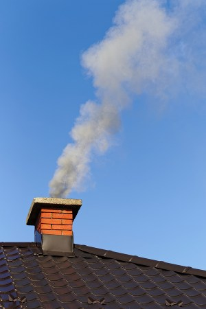 Chimney on a roof with smoke coming out of it.