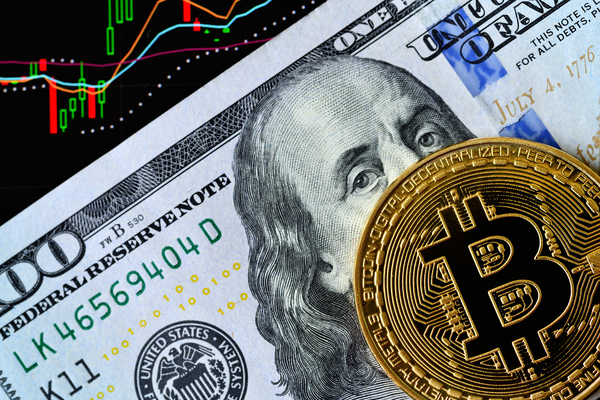 100 dollar bill and a gold coin with a bitcoin symbol.