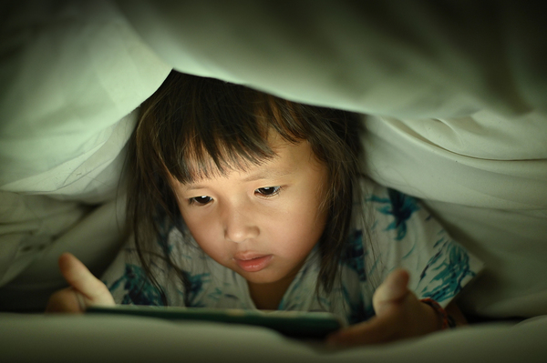 Young child looking at a tablet screen under blankets.