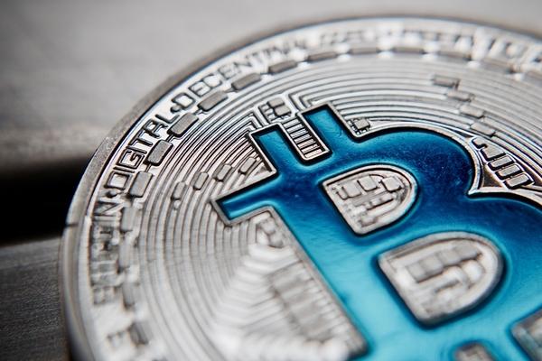 Silver Bitcoin coin with a blue B.