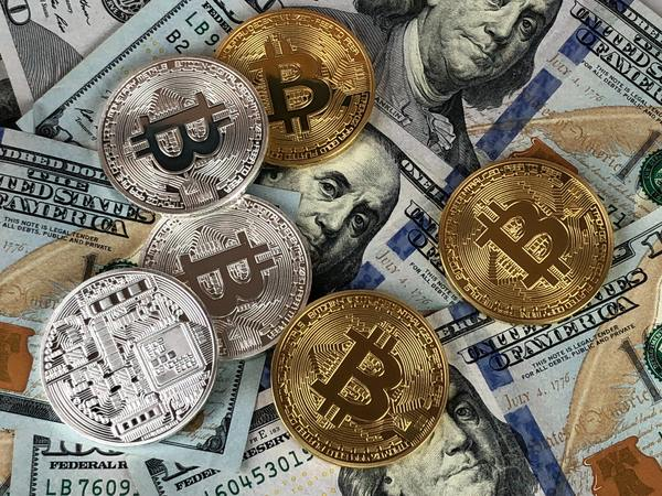 Gold and silver bitcoin coins and American paper money.