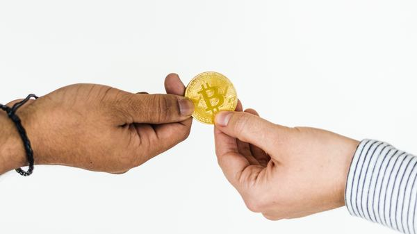 Two people holding a gold bitcoin coin.