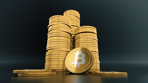 Gold bitcoin coins in three large stacks.